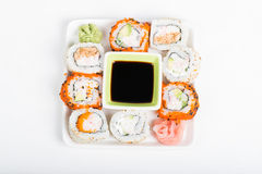 Different sorts of sushi on the plate, top view. Different sorts of sushi rolls with soy sauce on the plate stock image