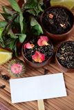 Different sorts of tea, mint and dry rose petals and a white card. For a text royalty free stock photo