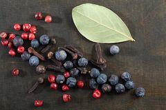 Different spice berries. Different spice berries with laurel on a dark wooden background royalty free stock photo