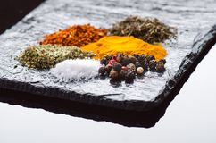 Different spices and herbs on a black slate. Indian spices. Ingredients for cooking. Healthy eating concept. Various spices on dar Stock Images