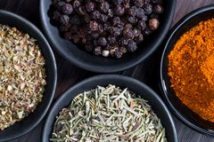 Different spices and herbs in spoons or bowls on a brown wooden Royalty Free Stock Photo