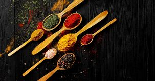 Different spices placed in spoons. From above view of colorful spices of different sort placed in spoons on wooden background stock photos