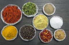 Different spices in shiny bowls on a dark wooden table Stock Photo