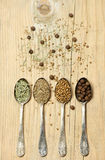 Different spices in silver spoons on wooden background Royalty Free Stock Image