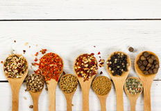 Different spices in wooden spoon on wooden background. Stock Photo