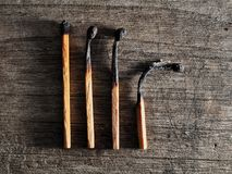 Different stages of match burning. Burnt matches isolated on wooden background. Creative background stock photo