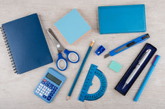 Different stationery tools of blue color on light wooden table Royalty Free Stock Images