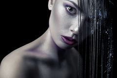 Different style of beauty. young beautiful fashion model with silver, purple, blue makeup and shiny silver jewelry chain on her fa. Ce. studio low key shot royalty free stock photos