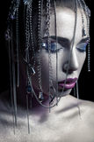 Different style of beauty. young beautiful fashion model with silver, purple, blue makeup and shiny silver jewelry chain on her fa. Ce. studio low key shot Royalty Free Stock Photo
