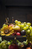 Different summer fruits in an iron bowl with a sunflower on a wooden background, close up Stock Image