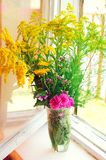 Different summer meadow flowers. Rustic interior. royalty free stock photography