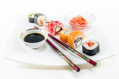 Different sushi rolls on white background. Different sushi rolls with chopsticks on white background royalty free stock photo