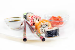 Different sushi rolls on white background. Different sushi rolls with chopsticks on white background stock photos