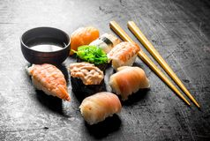 Different sushi with soy sauce and chopsticks. On dark rustic background stock photos