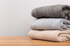 Different sweaters on a wooden table on a light background. Autumn and winter clothes stock photos