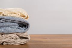 Different sweaters on a wooden table on a light background. Autumn and winter clothes stock photo