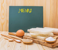 Different sweet baking on a table with blank board Royalty Free Stock Photo