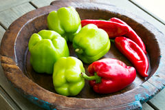 Different sweet bell peppers. Different sweet peppers on wooden plate Royalty Free Stock Photo