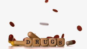 Different tablets pouring on dice spelling drugs stock video