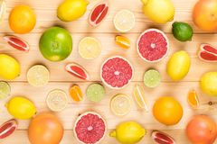 Different tasty citrus fruits on a light wooden table stock photography