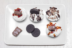 Different tasty cupcakes with biscuits and chocolate on a plate Royalty Free Stock Photography