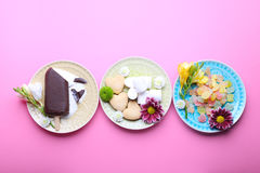 Different tasty sweets with flowers on pink background, top view Royalty Free Stock Image