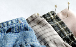 Different textures and colors of clothes with pins. On white background Royalty Free Stock Photo