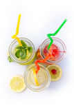 Different tips of lemonade in the jug with straws and lemons on white background Royalty Free Stock Photos