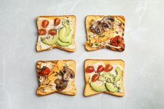 Different toasts with avocado, cherry tomatoes, mushrooms and chia seeds on grey background. Top view royalty free stock photo