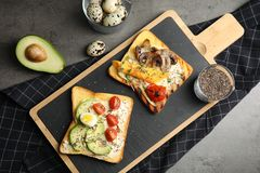 Different toasts with avocado, mushrooms, cherry tomatoes and chia seeds served on grey table. Top view stock photography