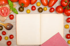 Different tomatoes, basil, wooden spoon and a book with text spa Royalty Free Stock Photos