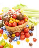 Different tomatoes in basket on white wooden table Royalty Free Stock Photography