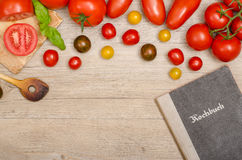 Different tomatoes with wooden spoon and recipe book Stock Photos