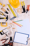 Different tools with clipboard and blueprint on wooden tabletop Stock Photos