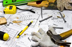 Different tools are lying on carpenter workbench. Busy hobby workbench. Different carpenter tools: saw, hummer, tape measure, level ruler, screwdriver are lying Stock Image