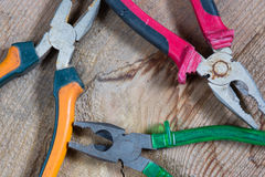 Different tools on a wooden background, pliers. Different tools on a wooden background Royalty Free Stock Photo