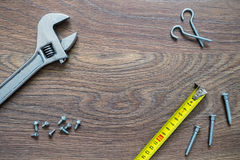 Different tools on a wooden background. Different tools (wrench, ruler, screws) on a wooden background. Fathers day card with copy space royalty free stock images