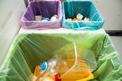 Different trash can with colorful garbage bags. Stock Photos