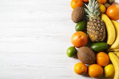 Different tropical fruits on white wooden background. Flat lay. Top view stock photos