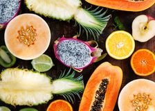 Different tropical fruits on a wooden table, papaya, dragon fruit, melon, orange, greiprut, kiwi, lime, pineapple. Top view stock photo