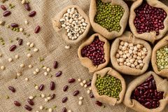 Different type of Bean seeds in sack bag, top view. Raw legume seed on sack cloth background stock photos