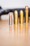 Different type of bullets. Close up view of different type of bullets and handgun. Shallow depth of field. Pistol out of focus. Vertical view stock photography