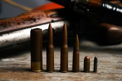 Different type of bullets and shotguns. On wooden background. Hunting ammunition and rifles, close-up Stock Photos