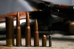 Different type of bullets and shotguns. On wooden background. Hunting ammunition and rifles, close-up Stock Photo