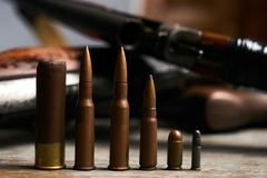 Different type of bullets and shotguns. On wooden background. Hunting ammunition and rifles, close-up Royalty Free Stock Photography