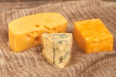 Different type of cheese on wooden background. Dutch cheese, French gorgonzola cheese and marble cheese on sackcloth. Food for dairy gourmet royalty free stock photography