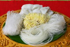 Different type of noodle on wood tray, on red back ground. stock image