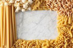 Different type of pasta make a frame around a white marble table with copy space for your text or logo. Different type of pasta make a frame around a white stock images