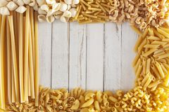 Different type of pasta make a frame around a white rustic wooden table with copy space for your text or logo. Different type of pasta make a frame around a royalty free stock image