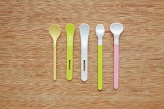 Different type of plastic spoons for babies on wood board background.  royalty free stock photos